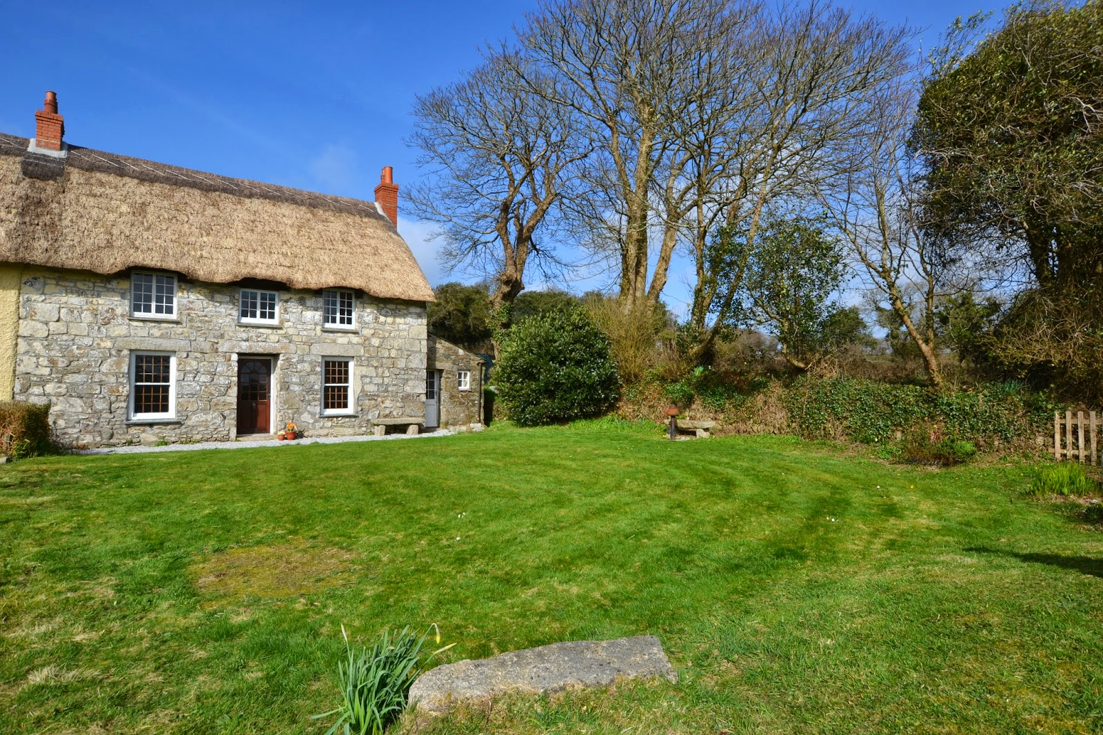 a pretty cottage with a large lawn in front