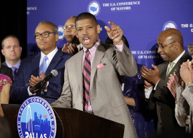 Kevin Johnson, at podium, Sacramento Mayor, President, The United States Conference of Mayors gestures as he responds to questions during a news conference at the annual meeting of the U.S. Conference of Mayors as Columbus, Ohio Mayor Michael B. Coleman, center left, Philadelphia Mayor Michael A. Nutter, right, show their support, Friday, June 20, 2014, in Dallas. (Credit: AP/Tony Gutierrez) Click to enlarge.