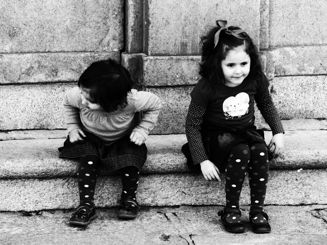 Two little girls wearing polka dots and sitting on church steps in Toledo, Spain.