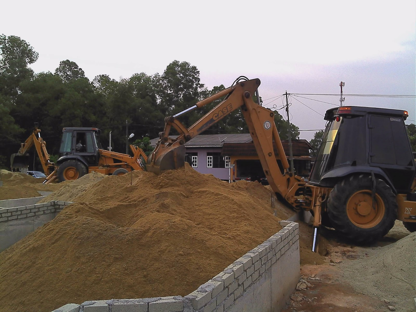 Mamasukkan pasir ke dalam tapak rumah yang telah dinaikkan sekaki