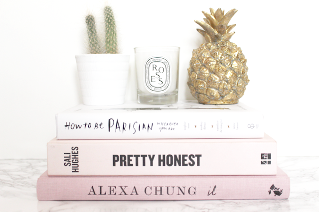 Cactus, pineapple and Diptyque candle on stack of pink books