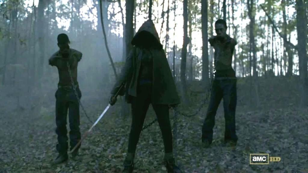 Michonne, cappuccio in testa e katana, porta con sé i due zombie incatenati, senza braccia e senza bocca
