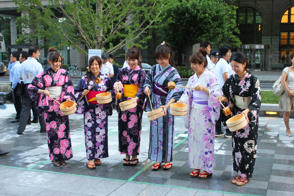 Women in yukata doing uchimizu.