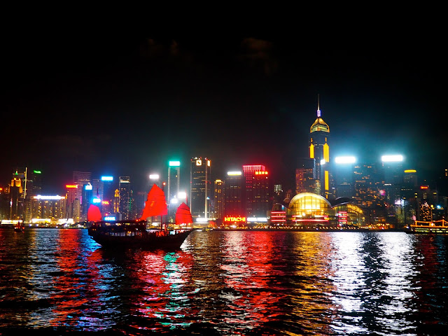 A Symphony of Lights | view of Hong Kong island and Victoria Harbour from TST promenade at night with traditional Chinese junk boat