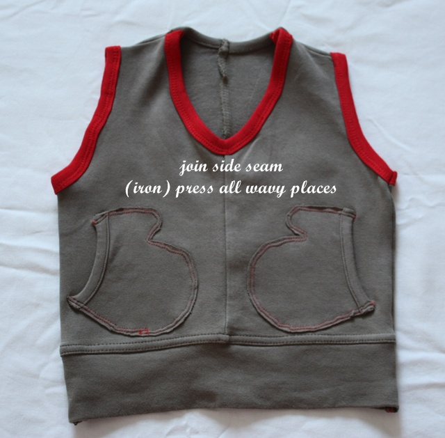 grey fleece vest with mitten shaped pockets traced in red stitching