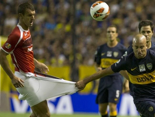 Аргентинец Сантьяго Сильва хватает за шорты мексиканца Диего Новаретти во время матча в Буэнос-Айресе.