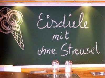 """Kreidetafeltext neben Eisbild:"""" Eisdiele mit ohne Streusel"""""""
