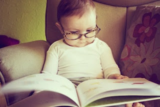 baby with reading glasses looking at a book
