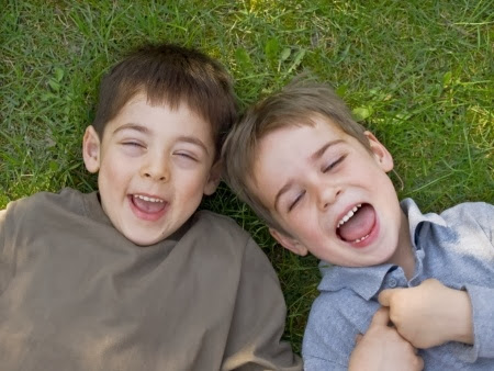 namc montessori encouraging positive behavior two boys laughing on grass