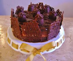 Torta de chocolate trufada com recheio de maracujá com arabescos.