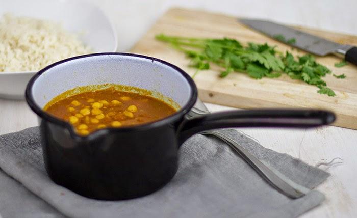 veganes Kichererbsen-Curry mit Tomaten in einem kleinen Topf, dazu gibt es Reis und Koriander