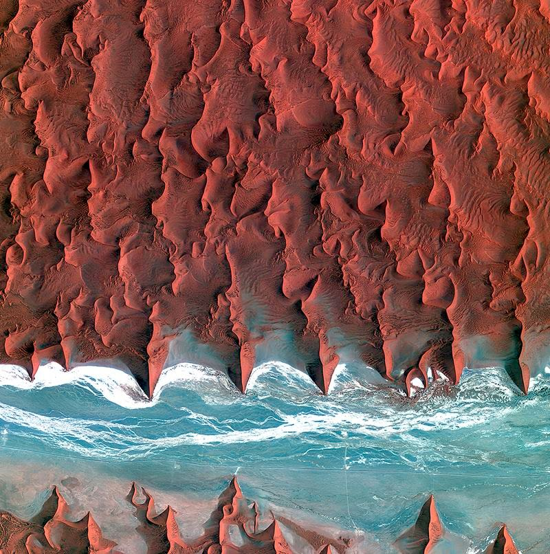 Korea's Kompsat-2 satellite captured this image over the sand seas of the Namib Desert on 7 January 2012. The blue and white area is the dry river bed of the Tsauchab. Black dots of vegetation are concentrated close to the river's main route, while salt deposits appear bright white. Running through the river valley, a road connects Sossusvlei to the Sesriem settlement. At the road's 45th kilometre, seen at the lower-central part of the image, a white path shoots off and ends at a circular parking area at the base of a dune. This is Dune 45, a popular tourist stop on the way to and from Sossusvlei. In this image, there appears to be some shadow on the western side. From this we can deduce that the image was acquired during the late morning. ESA supports Kompsat as a Third Party Mission, meaning it uses its ground infrastructure and expertise to acquire, process and distribute data to users.