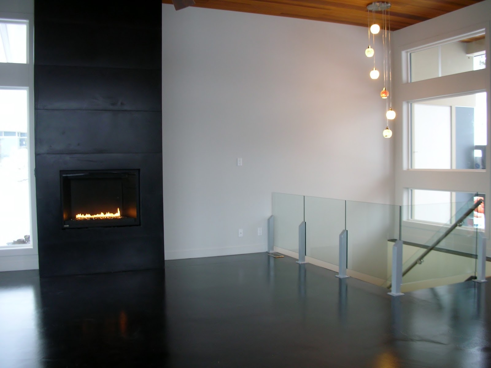 modern and super cool black concrete floor on wood subfloor with black stained concrete fireplace tiles made by artisans in kelowna bc canada by mode