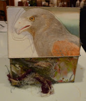 Two sides of box. One appears to have a bluejay in a leafy tree with a bluejay feather attached. Another side has a large white water bird, an Ibis or egret, about to dive into the water or take flight. Further image description in text.
