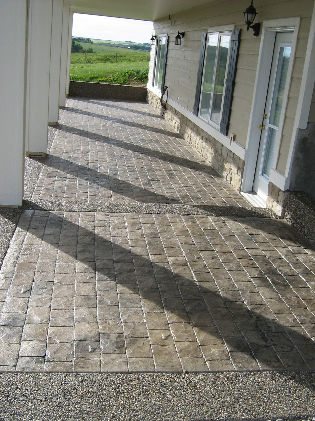 Sundre Concrete Works Walkout patio in cobblestone with exposed