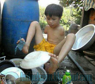 seorang anak kecil sedang mencuci piring