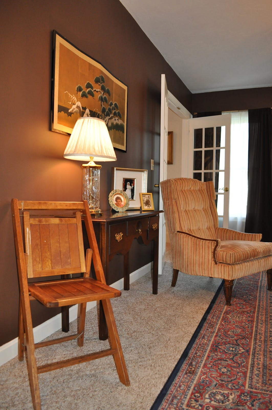 Brown gold and orange living room - A Few Family Pictures Personalize The Space With Different Frames Of Gold