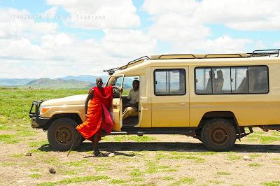 Seorang lelaki Maasai berfoto di depan mobil kami