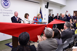 Director Mayorkas (standing left) applauds as New York District Director Andrea Quarantillo and Congresswoman Carolyn Maloney cut the ceremonial ribbon