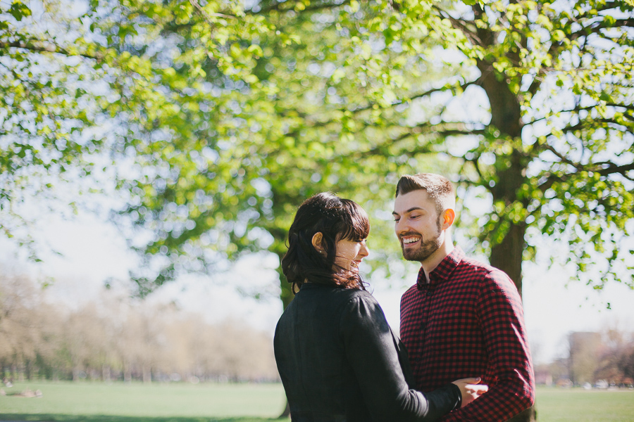 Young couple Jade and Jon stand by a leafy tree in Victoria Park for their engagement shoot