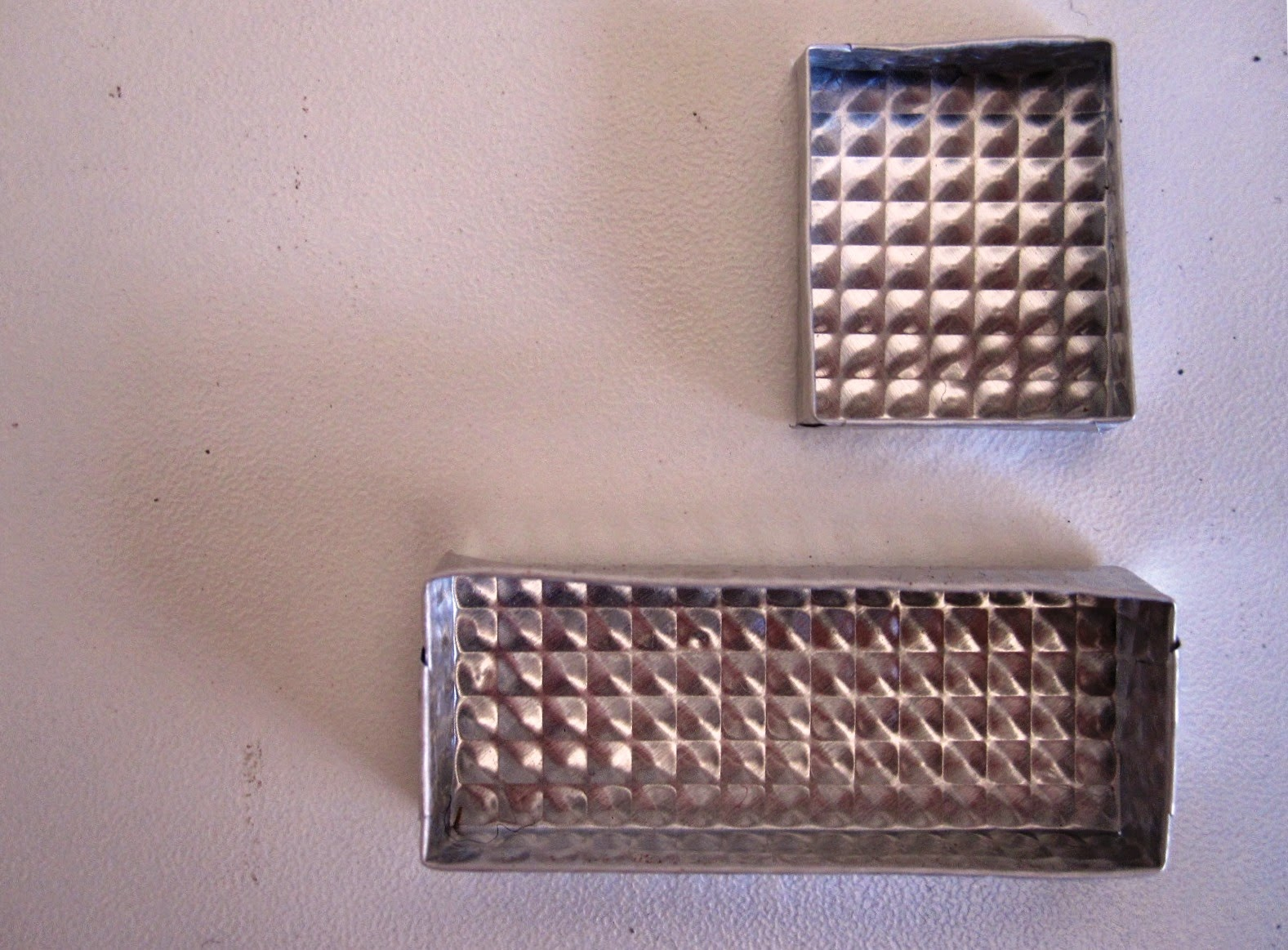 Two silver-coloured embossed metal dolls house miniature trays, one rectangular and one square.
