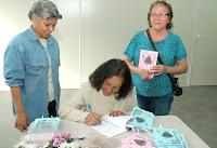 A autora Romilda dos Santos Veiga autografa o seu livro durante lançamento