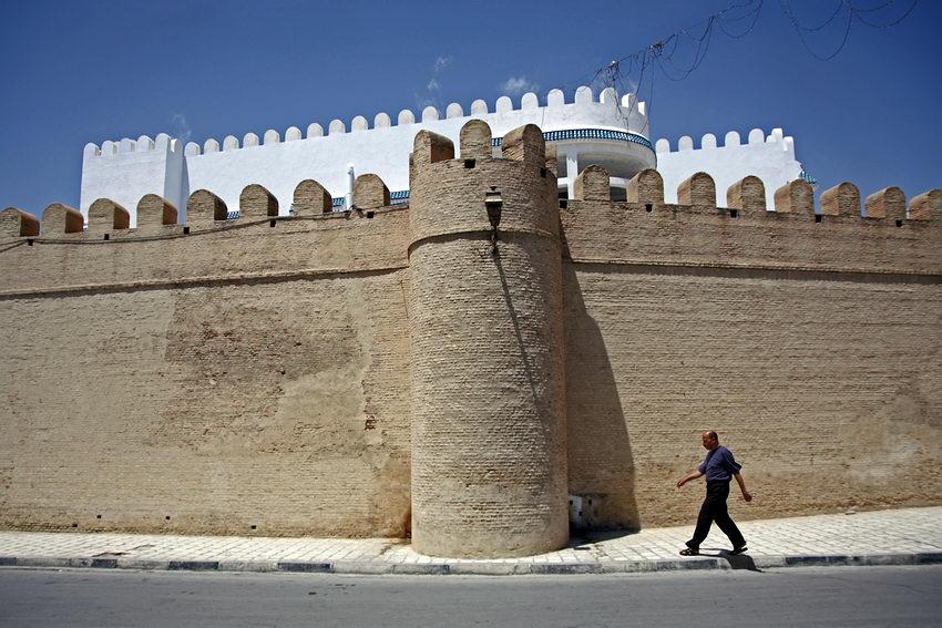 Homem caminhando nu passeio ao lado de uma muralha em pedra. Por detrás desta uma outra em branco contra o céu azul