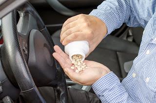 Man taking pills before driving.