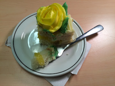 "A square slice of vanilla cake with lemon frosting and a yellow flower sits on a plate with one bite resting on an adjacent fork. The caption reads: ""Oh, this? Piece of cake."""