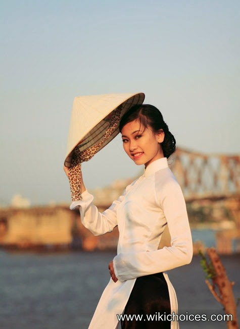 Ngoc Ha in beautiful long dress, holding a conical hat tilted slightly in the sunset