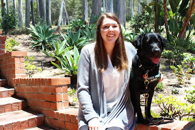 Christina sits on a brick stairway smiling with her arm around a black Lab guide dog puppy.