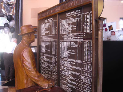 Sculpted figure of a man stands looking at a large metal sign listing train times