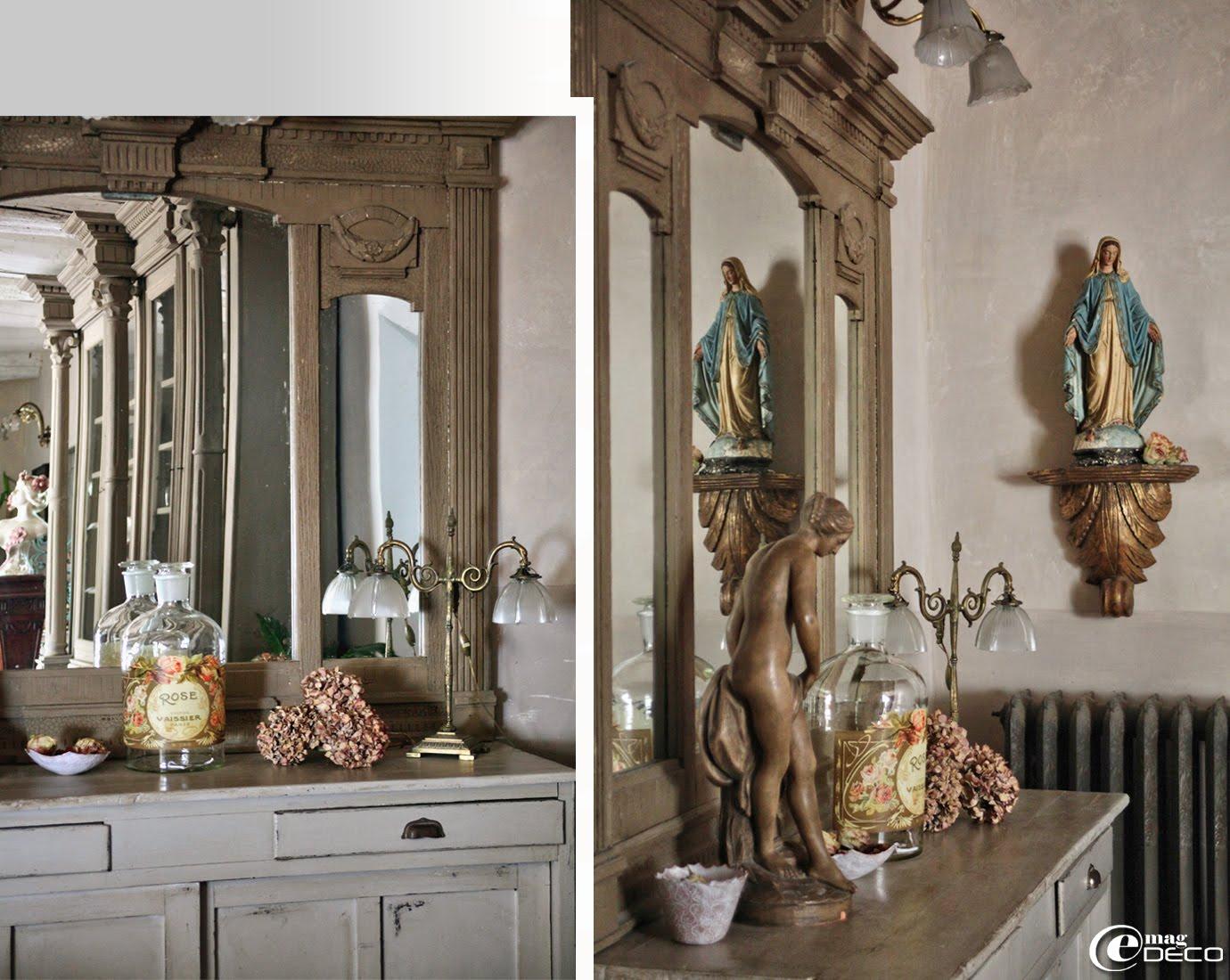 Une des nombreuses vierges en plâtre dont Philippe fait collection près d'un vieux meuble de restaurant avec portes coulissantes