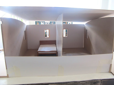Front view of a taped-together modern dolls' house miniature kit, with a cardboard half-wall and two small rooms, one with a bed in it.