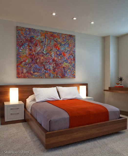 a bed looks beautiful with round dim lights and complete with abstract wall mounted painting