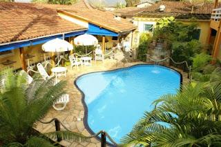 Aréa com piscina com cascata e hidromassagem, uma bela área verde, churrasqueira, e kit praia com cadeiras e guarda-sóis
