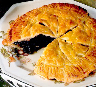 Classic pie of blackcurrant or redcurrants with a slice removed served as a dessert or teatime treat