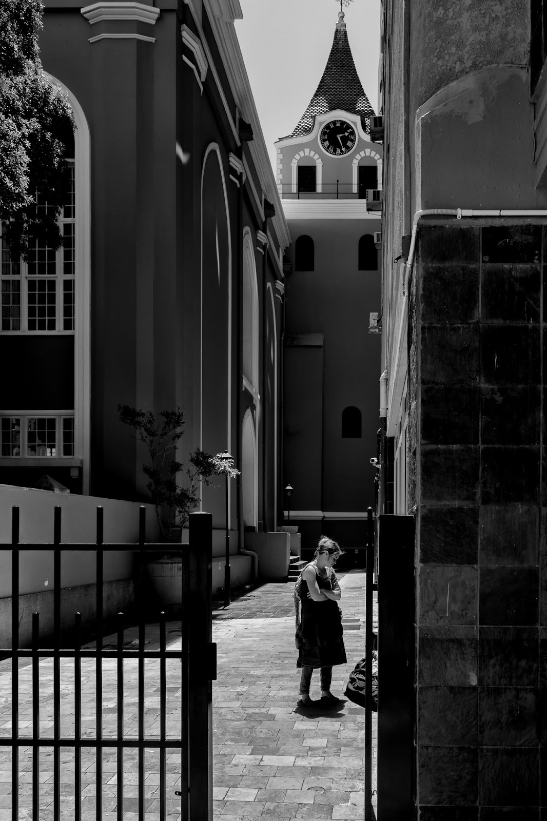 A young woman waits outside a church in this street photograph from Cape Town