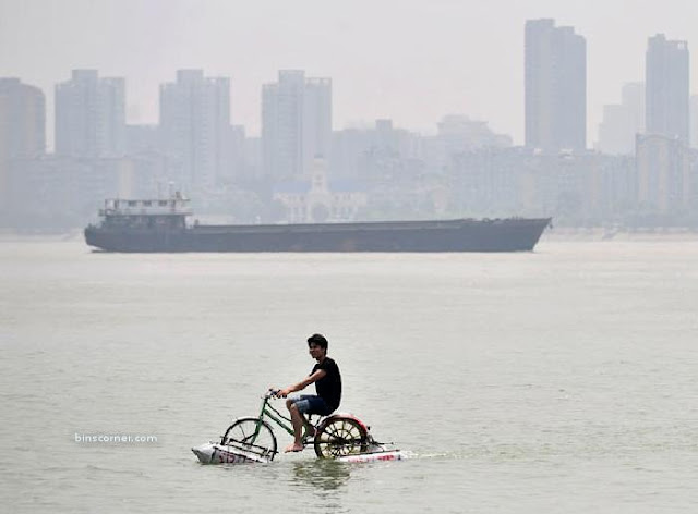 Lei Zhiqian rides a modified bicycle across the Hanjiang River