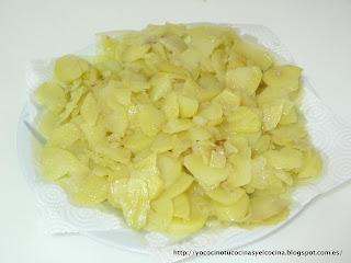 escurriendo patatas ya cocidas en aceite