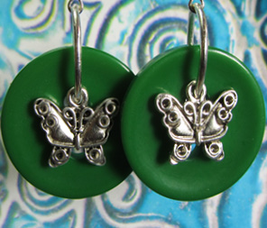 Bold drop dangle earrings have butterfly charms layered over big green buttons