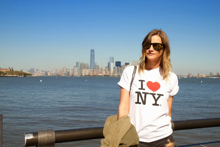 Vanocuver Fashion Blogger, Alison Hutchinson, at the statue of liberty, wearing an I heart NY top, One Teaspoon Hawks shorts, a silver valentina botkier bag, and off-white converse sneakers