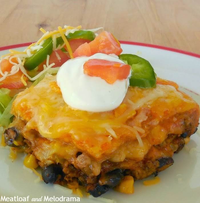 layerd tortilla casserole with meat beans cheese and corn on a dish