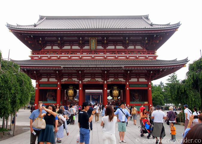Tourists posing in front of the Thunder Gate, entrance to Sensō-ji temple in Asakusa Tokyo