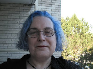 Full-face portrait of a fat white trans woman in her 40s, with chin-length curly blue hair