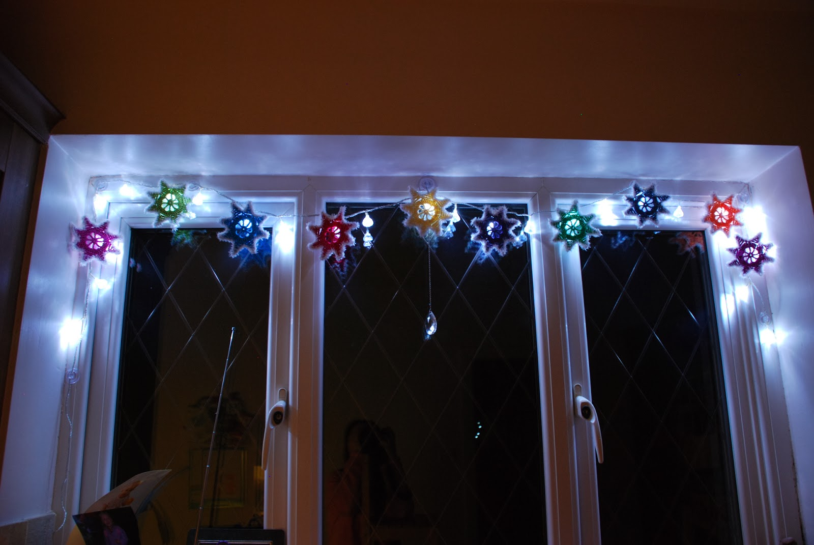 image of fairy lights with colourful crocheted stars for a winter  garland