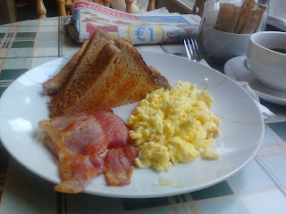 Bacon and scrambled eggs with brown toast, Royal Cafe, Galway, Ireland  - served on a white place, photographed with the Galway Advertiser newspaper in the background