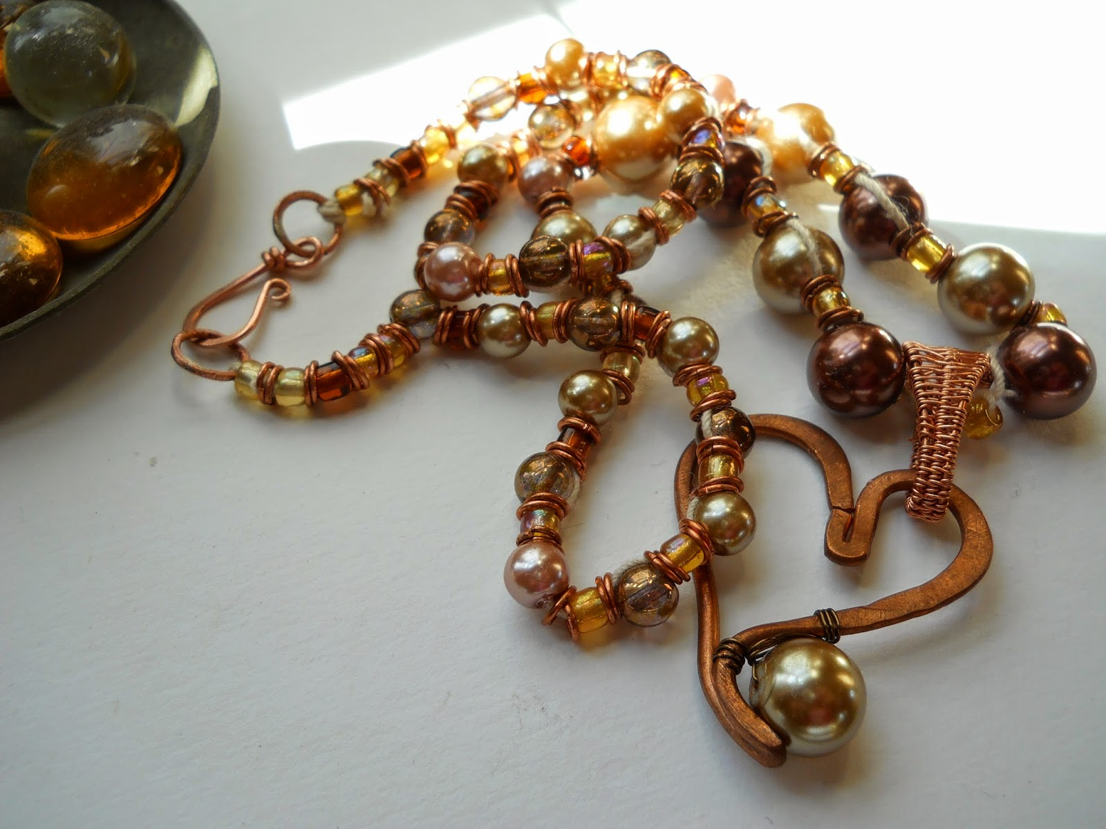 Glass beads and Pearls in warm rich coppery tones with copper accents and copper heart pendant.