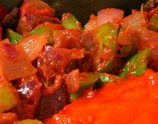 Tomato Sauce Being Stirred into Veggies