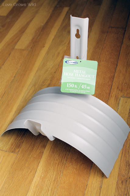 LoveGrowsWild.com   Make this DIY Garden Hose Holder to add great curb appeal to your home! #diy #garden # home